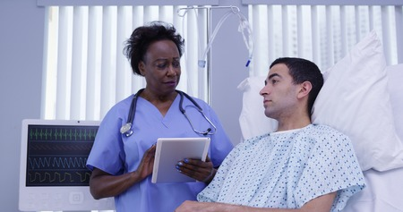 Mid aged African nurse checking on male patient with electronic notebook tablet Stock Photo