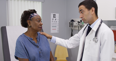 Young latino doctor discussing health problems with senior African woman