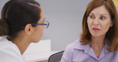 Closeup of female senior patient talking with young doctor in her office