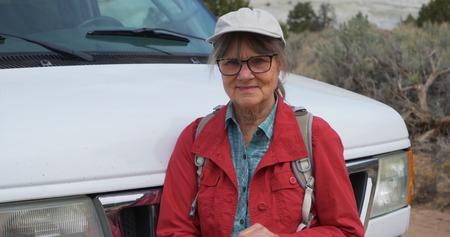 Close up portrait of joyful elderly woman in retirement outdoors in nature