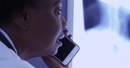 Mid aged black MD talking on mobile phone with patient about x ray Foto de archivo - 110930628