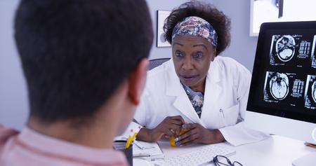 Senior African doctor prescribing medication to male patient with brain anomaly Foto de archivo - 110930667