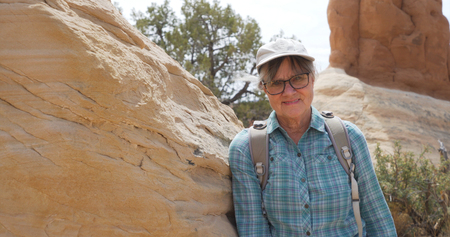 Closeup portrait of happy elderly woman with backpack rests in sandstone canyon Imagens