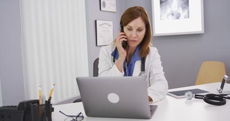 Senior medical physician talking on smart phone and using laptop computer Stock fotó