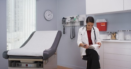 Close up of lovely latina doctor reviewing patients file indoors medical clinic