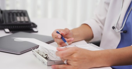 Close up of female licensed MD using clipboard inside her office