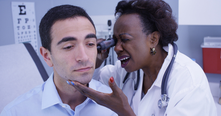 Portrait of African senior doctor using otoscope to inspect young patients ear Archivio Fotografico