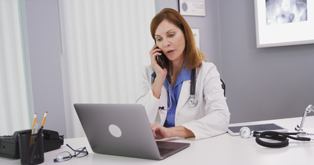 Attractive mid aged doctor using latop computer while talking on smartphone Stock fotó
