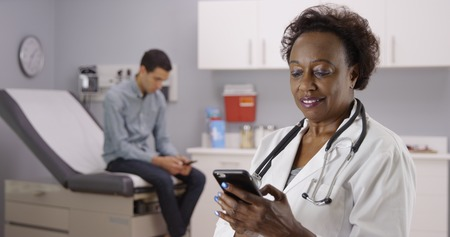 Middle aged African doctor using mobile phone to text while male patient waits