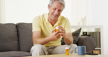 Healthy middle-aged man reading prescription bottle and talking on his cell phone