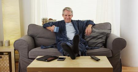 Vrolijke man van middelbare leeftijd ontspannen op de bank met voeten op tafel