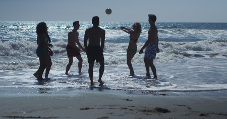 Silhouette of group of interracial friends playing volleyball in the beach water
