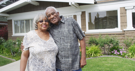 Retired African couple embracing each other on yard