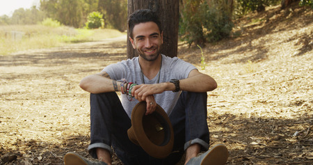 Attractive Hispanic man sitting outdoors smiling at camera Stock Photo