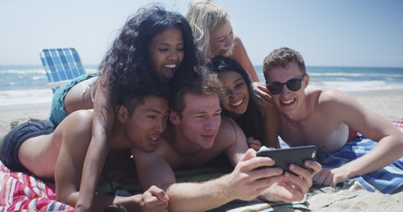 Young interracial group of friends lying on the beach taking selfie 版權商用圖片