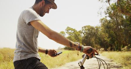 Sexy Hispanic man sitting on bike and using smartphone