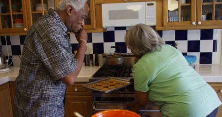 Elderly black woman baking cookies 스톡 콘텐츠