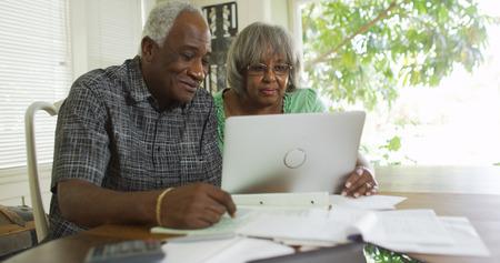 Reifes afrikanisches Paar liest auf ihrem Laptop