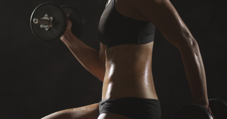 Active Asian woman lifting dumbbells weights and sweating
