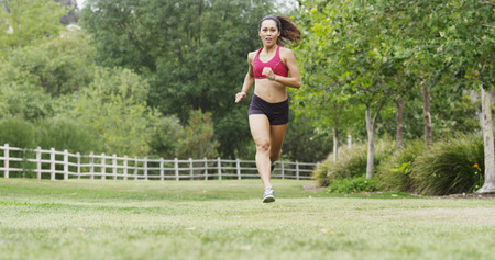 Athletic Young Asian woman running across grass field at the park