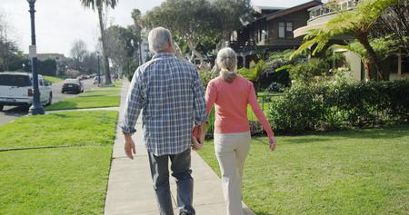 Senior couple walking through neighborhood Stok Fotoğraf