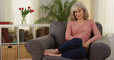 Pretty mature woman smiling couch