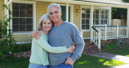 Senior couple smiling in front of house Stock Photo