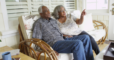 Elderly African couple looking and sitting from a couch