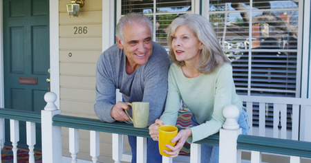 Elderly couple on porch smiling Imagens