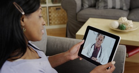 Middle aged Black woman consulting doctor on tablet Stock Photo
