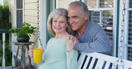 Sweet mature couple relaxing on porch talking Фото со стока
