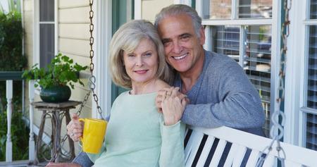 Couple de personnes âgées souriant sur le porche en regardant la caméra