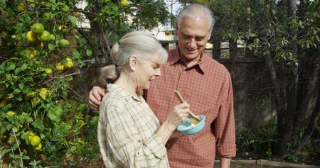 Senior couple standing eating in garden