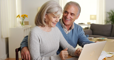 Happy mature couple using laptop computer to pay bills 免版税图像