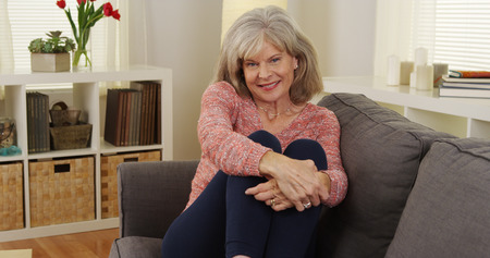 Mature woman sitting couch smiling 免版税图像