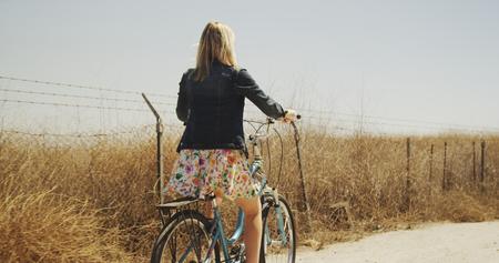 Rear view of young woman riding bike along wheat field 免版税图像