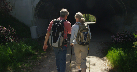 Senior white couple backpacking on a trail