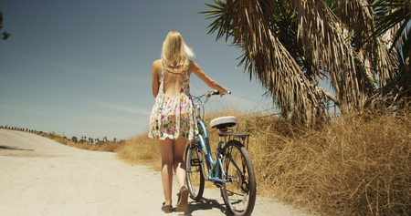 Beautiful young white woman walking bicycle on dirt road