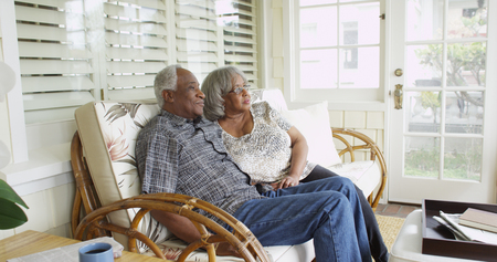 Mature black couple sitting on couch looking away 免版税图像