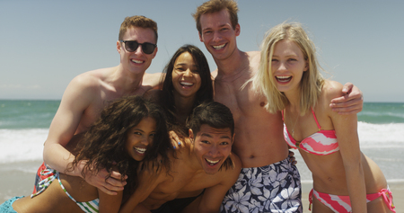 Portrait of young group of friends on the beach smiling at camera