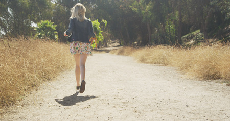 Young attractive caucasian girl running on dirt road