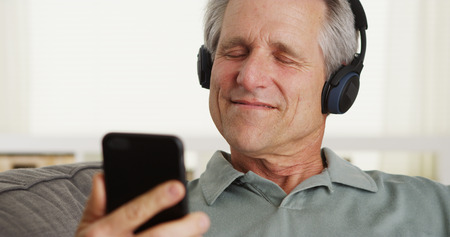 Happy middle-aged white man enjoying music on mp3