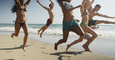 Healthy Group of interracial friends running along beach shore jumping together