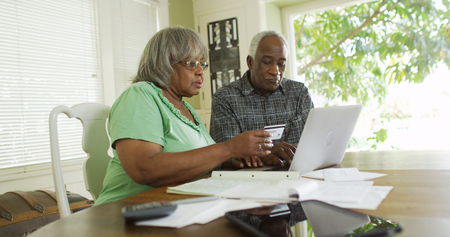 Senior black couple paying credit card online