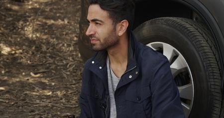 Attractive Hispanic man waiting for road assitance 免版税图像