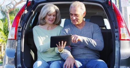 Elderly couple using tablet deciding where to go 免版税图像