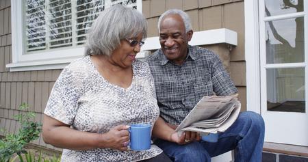 Happy retired African American couple reading newspaper Stock Photo
