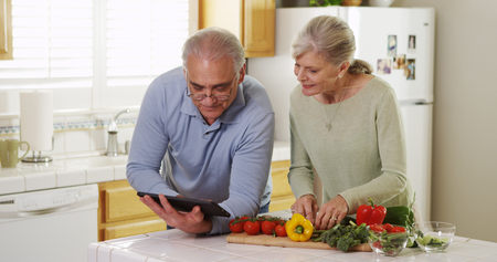 Senior couple using tablet and cooking