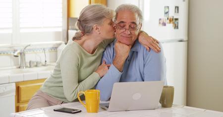 Senior couple using laptop computer in kitchen 免版税图像