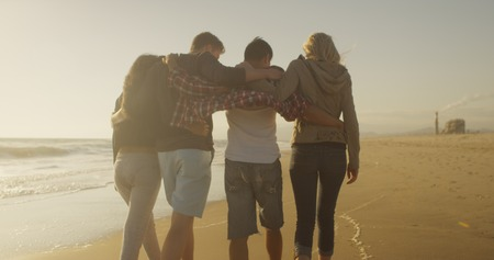 Group of friends walking along the shore together 免版税图像